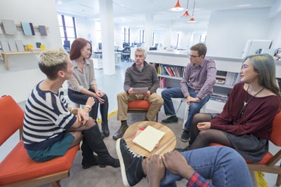 Informal business meeting. Group of peopleseated in circle in modern office. Design studio brainstorm.